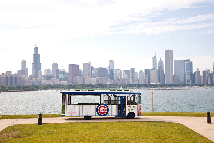A picturesque view of the #Cubs trolley against the Chicago city skyline.