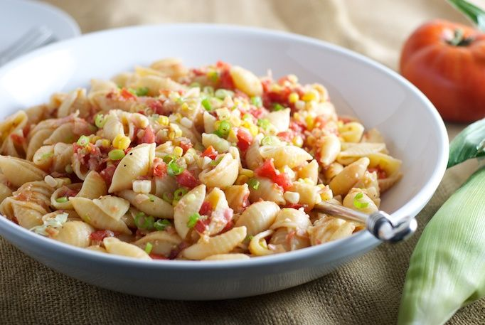 Summer pasta with raw tomato sauce, bacon, and corn