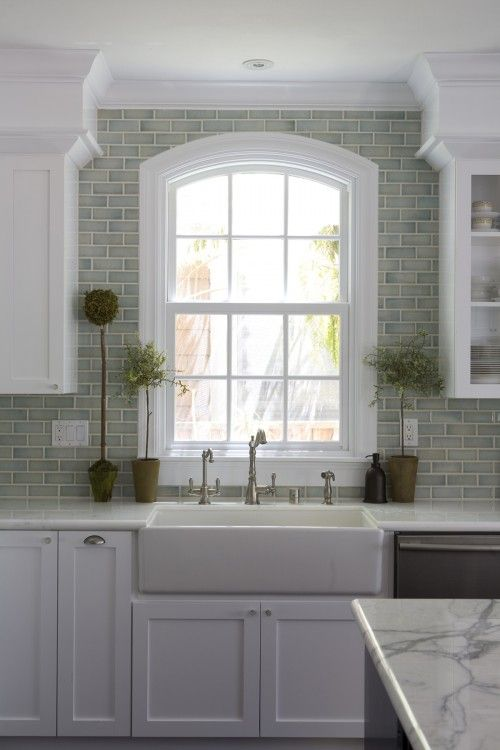 White cabinets, full wall backsplash in watery green.