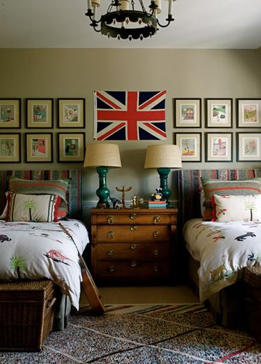fun boy's bedroom design with union jack flag, twin beds, vintage chest nightstand, peacock blue lamps, dinosaur bedding, wicker baskets, blue lamps and tan walls paint color.