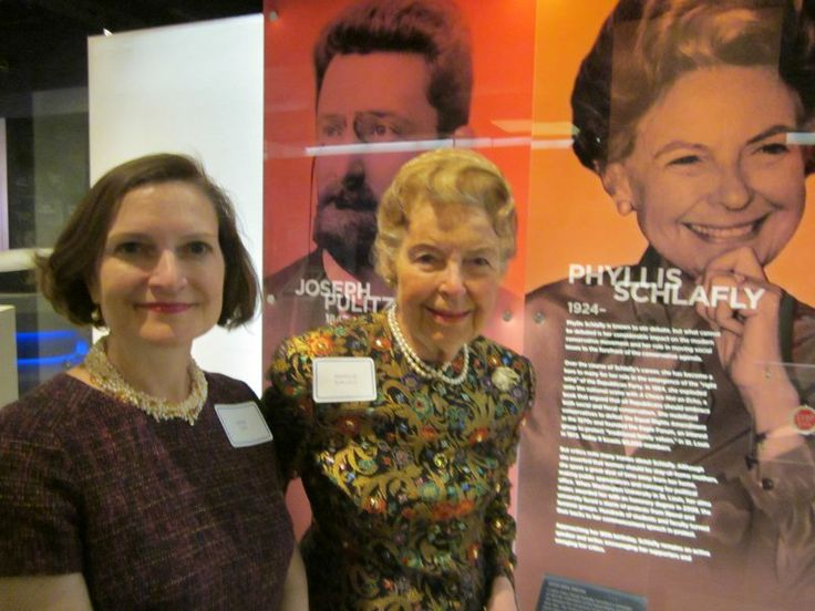"""PHYLLIS HONORED AT ST. LOUIS' 250TH BIRTHDAY CELEBRATION. The Missouri History Museum is celebrating St. Louis' 250th birthday with a special exhibit featuring highlights of 50 people, 50 places, 50 moments, 50 images, and 50 objects. Phyllis is one of the 50 people featured in the exhibit. There is a nice picture of her along with her bio and a """"Stop ERA"""" pin. The exhibit is open through February 2015.   Pictured: Phyllis & Anne with Phyllis's exhibit, 2014"""