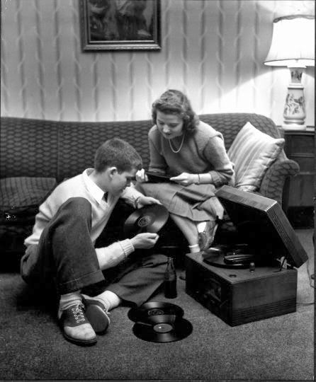 Teens in the 50s, sweaters, skirts and saddle shoes, playing records in the den. Nina Leen/Time Life picture