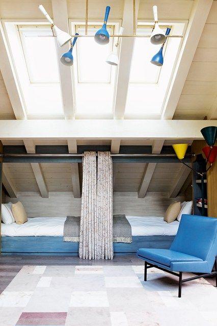 Habitación infantil en la que se han dispuesto cortinas en las camas para separar las dos zonas de descanso. Fuente:  houseandgarden.co.uk