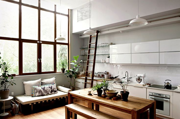 Tall ceiling, glossy white cabinetry, and wooden kitchen table.