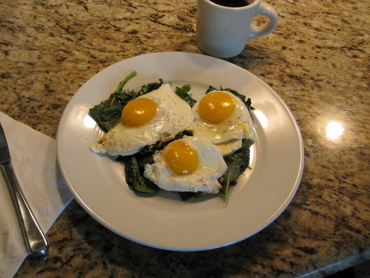 up a quick breakfast of eggs sunny-side up on greens (baby spinach ...