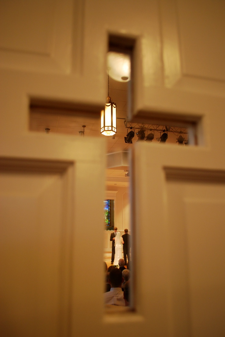 Picture of the wedding going on through the cross in the door of the church