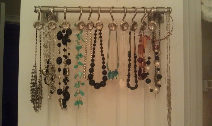 ... back of linen float door. Necklaces hanging on shower curtain hooks