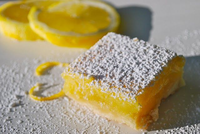 For the crust:1/2 pound unsalted butter (at room temperature)1/2 cup granulated sugar 2 cups flour1/8 teaspoon kosher salt  lemon layer:6 extra-large eggs  2 1/2 cups granulated sugar  2 tablespoons grated lemon zest (4-6 lemons)  1 cup freshly squeezed lemon juice  1 cup flour    Confectioners' sugar, for dusting.    Pre-heat oven to 350°F and liberally butter a 9x13 by 2 inch baking sheet.    For the crust, cream the butter and sugar until light in a bowl of an electric mixer fitted with a paddle atta...