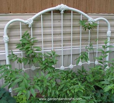 Old iron bed frames and metal gates with character look wonderful in gardens with blooming vine to climb on them.....Love this!!