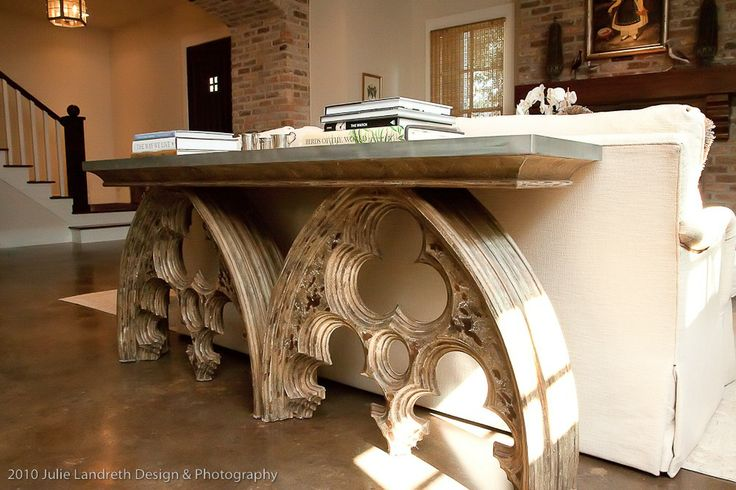 A zinc topped arched element console table sits behind the sofa, dividing the living area from the dining area. --  Cote de Texas