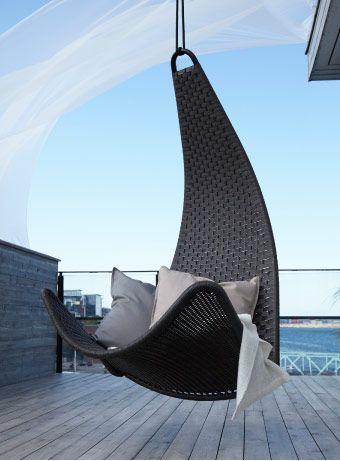 Brun hängande stol med grå kuddar