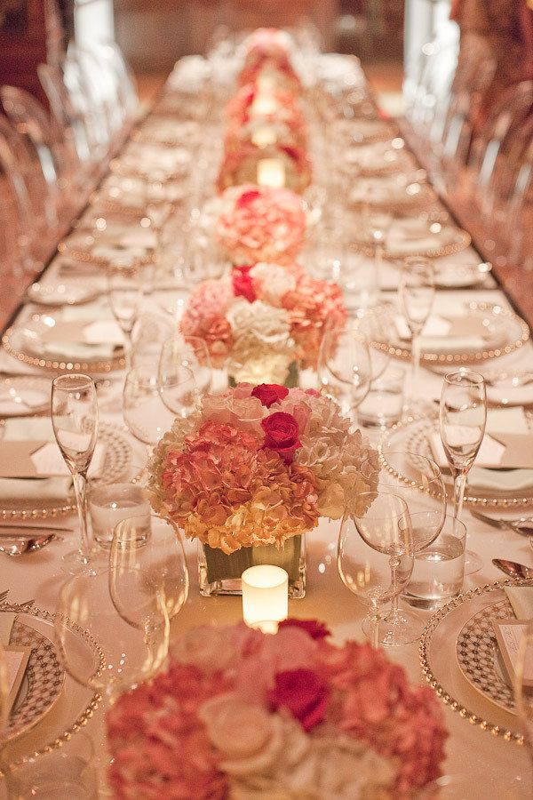 Beautiful low square vases of hydrangea and roses with gold place setting accents.