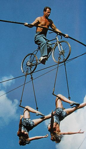 1950s Man Shirtless on highwire practice bicycle with two women cirucs performers