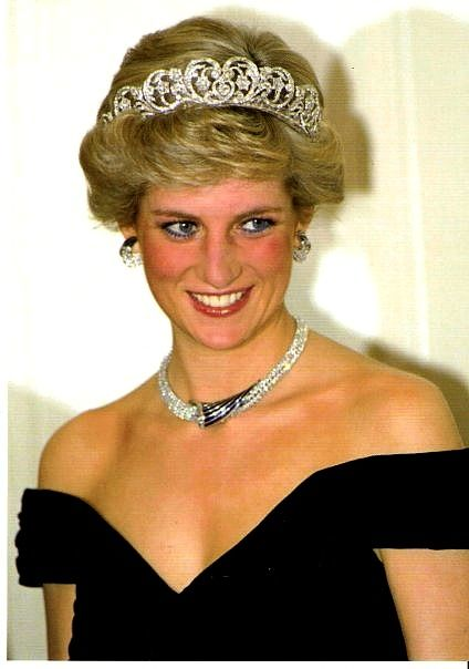 Diana, Princess of Wales, wearing the Oman Suite, which includes a sapphire and diamond necklace, earrings, and bracelet. The crescent shaped diamond earrings were given to Diana by the Sultan of Oman during the couple's visit to Oman in November 1986. In this photo, Diana is wearing the necklace and earrings at a formal banquet in Germany in November 1987.