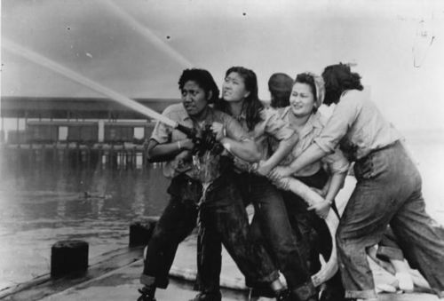 Female volunteer firefighters attempting to douse the flames at Pearl Harbor, December 7 1941.