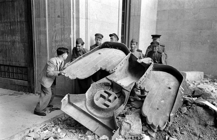 Unpublished. Russian soldiers and a civilian struggle to move a large bronze Nazi Party eagle that once loomed over a doorway of the Reich Chancellery in Berlin.