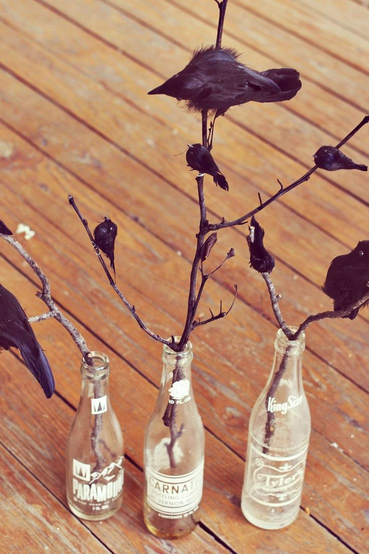 Black crow centerpiece in vintage soda bottles