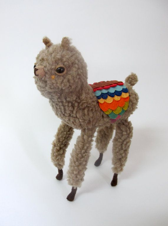 small wooly alpaca in a feathered rainbow saddle by catrabbitplush