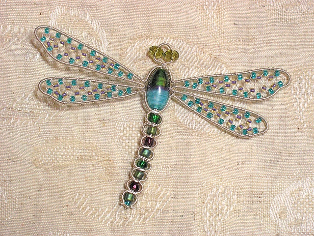 Dragonfly brooch; outline complete, wings netted.