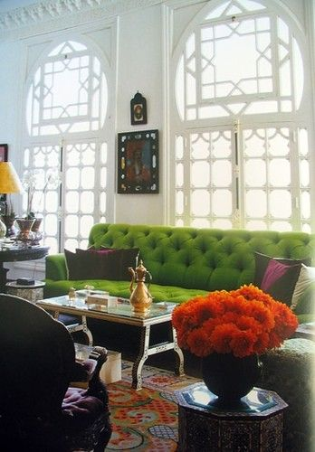 That green couch is gorgeous. The purple cushions and orange flowers really set it off.