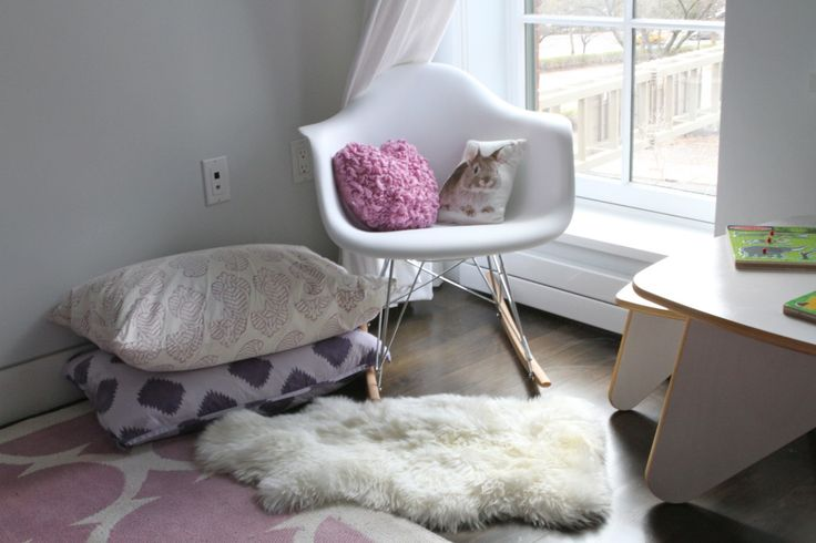 Mod rocking chair with pillows and faux fur rug - it creates a cozy and cute corner for nursing or reading! #nursery #nook