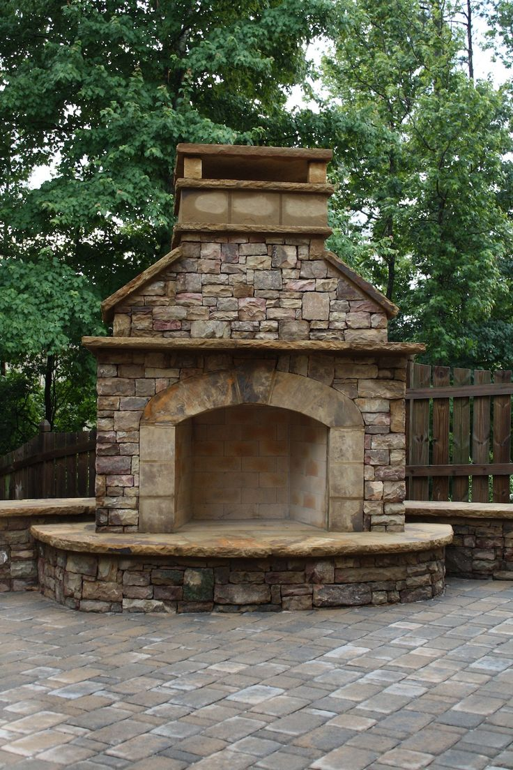 Stacked Stone Outdoor Fireplace With Hearth And Seating Wall