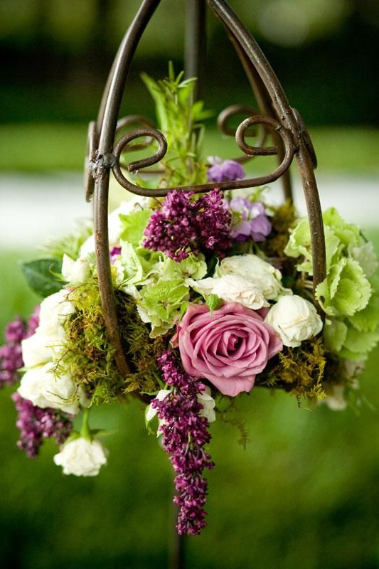 Playing with Nature.  A bronzy lantern frame holds floral in shades of purple, pink and green.  Utilized with a lantern hanger, this would make a beautiful centerpiece.