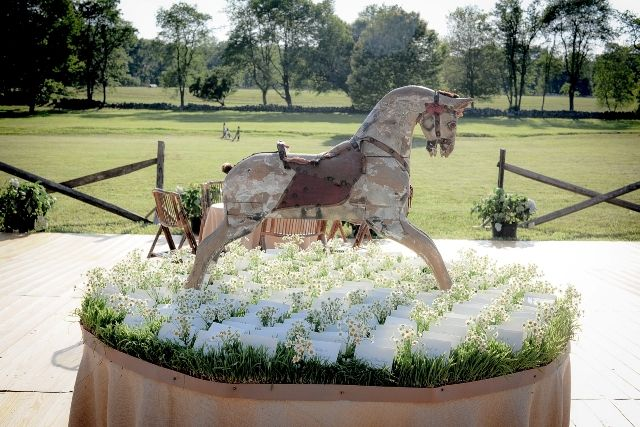 Vintage rocking horse for escort card display. Rustic horse jumps in the background.