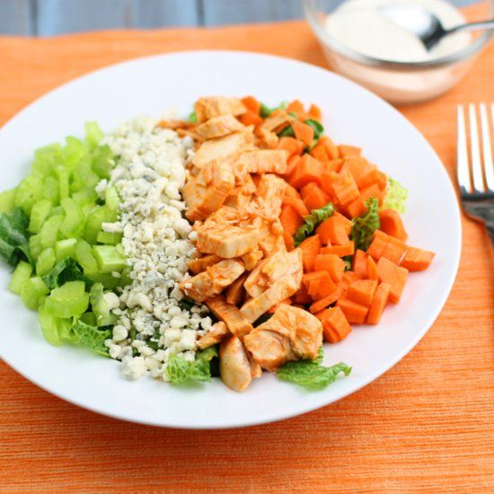 Buffalo chicken wings on a crisp refreshing salad complete with celery ...