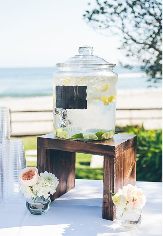 Super cute drink dispenser and stand at wedding ceremony. #drinkstation #weddingceremony #weddingchicks Captured By: Vitae Weddings ---> http://www.weddingchicks.com/2014/04/29/pastel-pink-wedding/