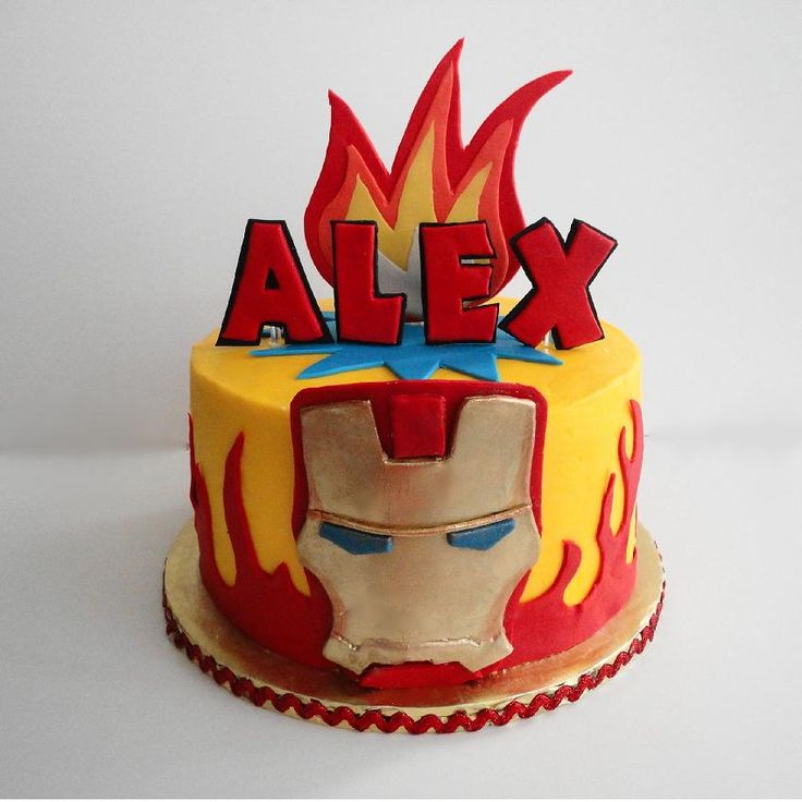 "Iron Man Avenger cake - French vanilla with raspberry filling and buttercream frosted 8"" round. One of three Avenger theme cakes for 2 little boys.  Fondant flames, gum paste hand-cut letters and fondant iron man mask dusted with ultra gold luster dust and lemon extract."