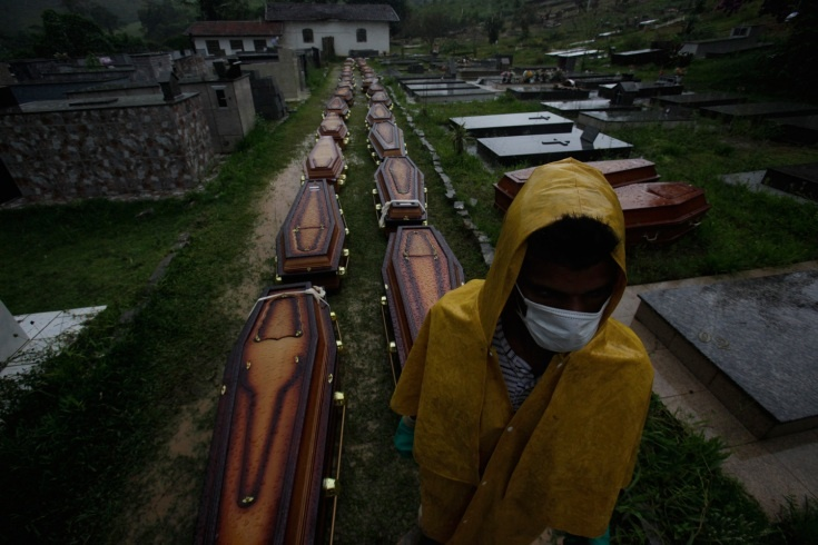 A worker stands next to coffins of victims of landslides at a cemetery in Nova Friburgo. Nearly four days after rains sparked floods and massive landslides, officials in the Brazilian town of Teresopolis were still struggling to cope with the catastrophe that killed at least 564 people in the region north of Rio de Janeiro.