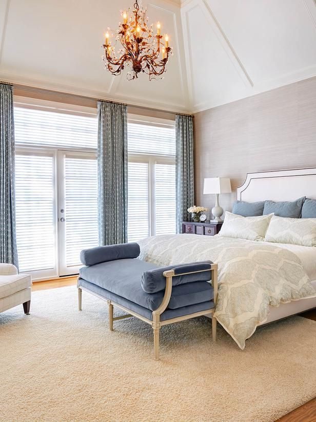 Paired with soft gray grasscloth, creamy white bedding and a sparkling chandelier, this French-inspired bedroom looks like a high-end hotel suite. Design by Rebecca Driggs