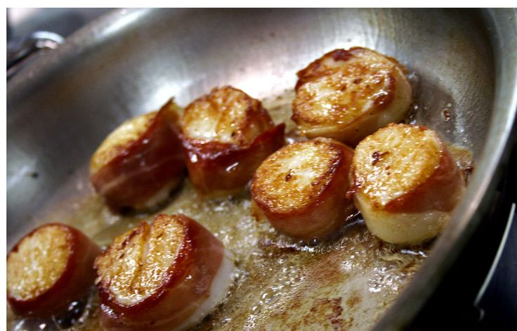 Prosciutto wrapped scallops sautéing in butter and olive oil