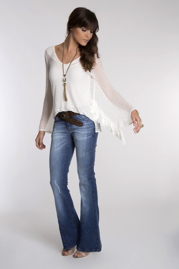 Malha rendada branca com franjas de rayon nas mangas, mix de correntes em ouro velho com pingente de pedra e tassel, e calça jeans flare com recortes.
