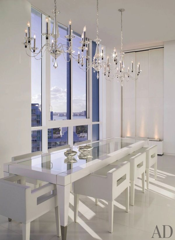 All white #dining room in a #contemporary #condo with three beautiful #chandeliers