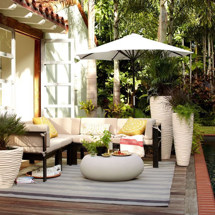 West Elm wood slat sectional, pebble coffee table, sunburst and sundial outdoor pillows and textured stone planters - easy and done!