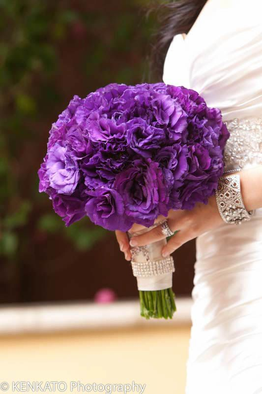 Beautiful purple bridal bouquet—it really pops against the white dress!