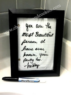 Write notes on cheap frame with scrapbook paper backing.  Blogger keeps this in their bathroom.  Too cute.