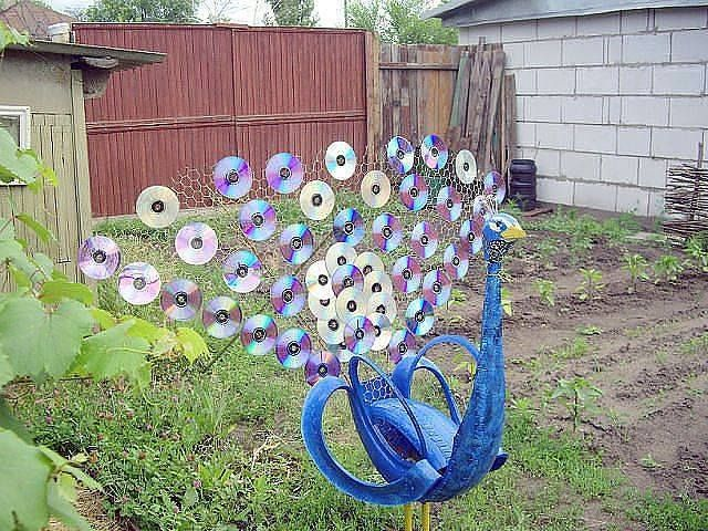 Old cd 39 s and tires into a peacock yard art from junk for Used tire yard art