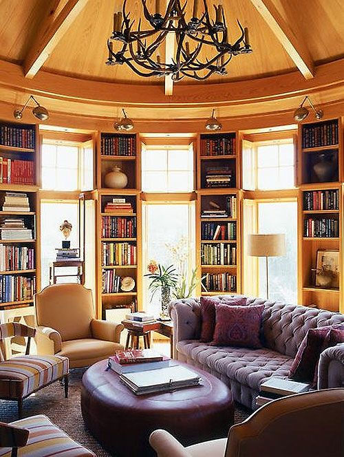 love this round room...the bookcases are broken up by the windows and surround the room...great idea...and the purple furnishings...WOW