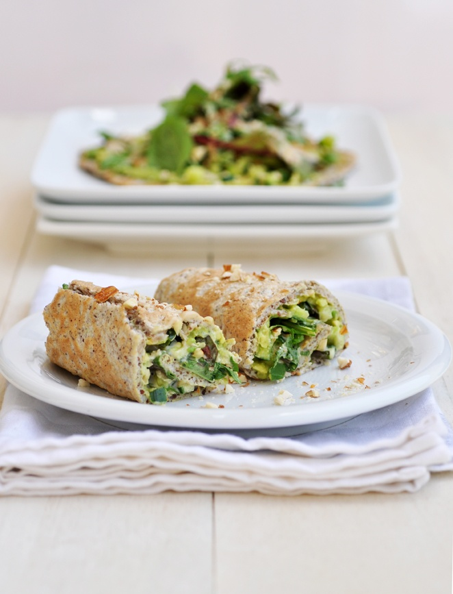 Summer wraps filled with avocado, cucumber, nuts & seeds and tahini sauce