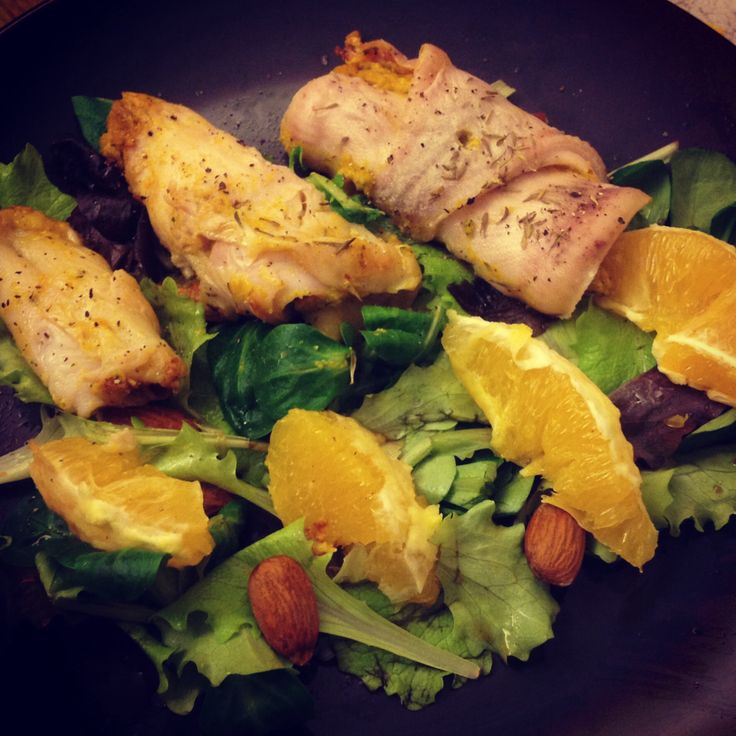 Baked flounder rolls with carrot and almond filling, salad and orange ...