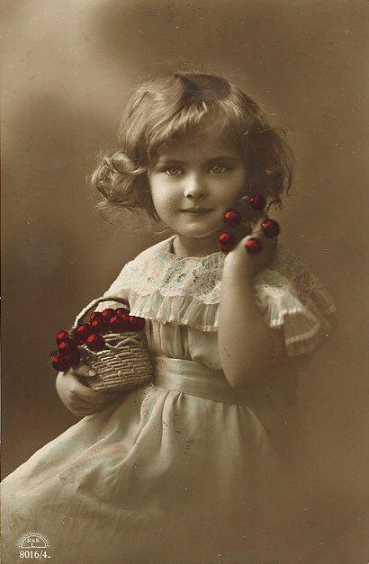 Victorian Child. Little girl holding cherries.