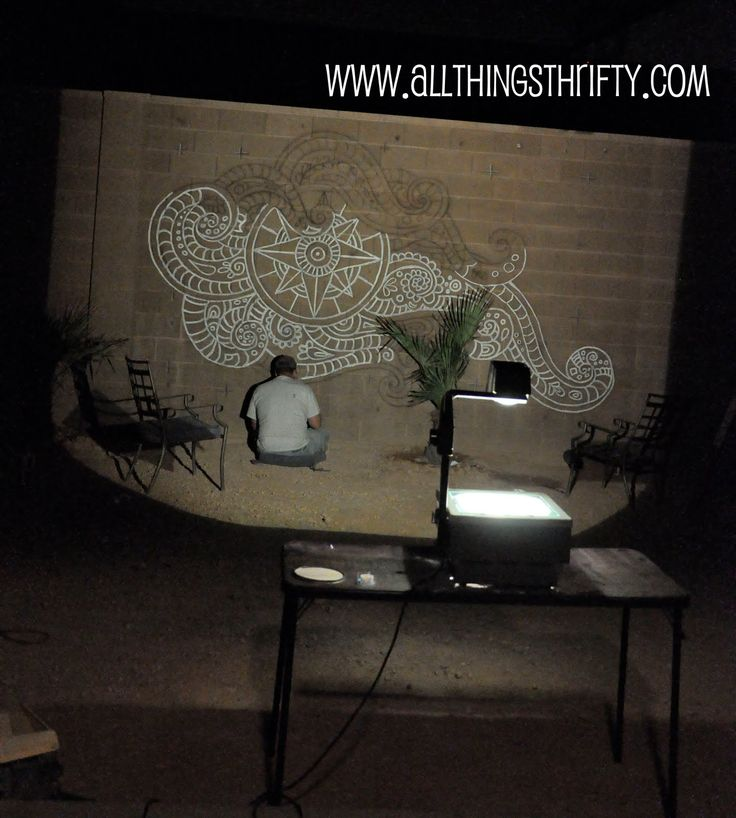 using an overhead projector to paint a mural on an outdoor brick wall. Black Bedroom Furniture Sets. Home Design Ideas