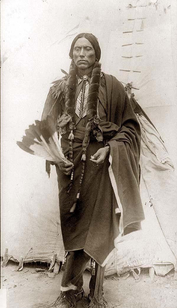 Quanah Parker, Comanche Indian Chief, full-length portrait, standing, facing front, holding feathers, in front of tepee. It was taken in between 1909 and 1932.