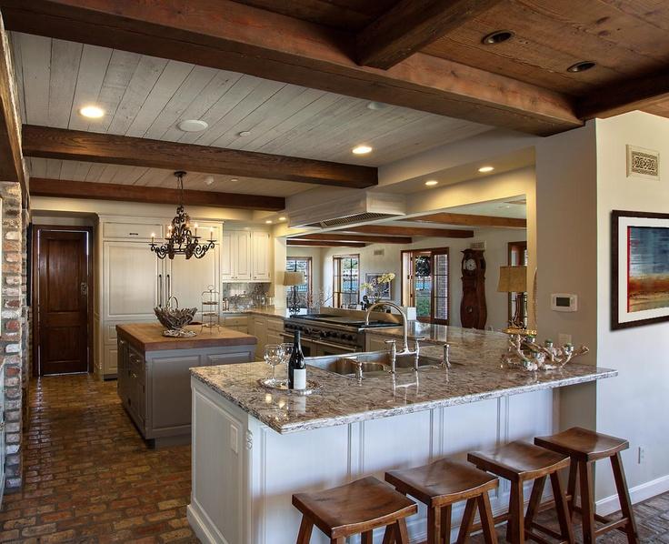 Distressed, cream kitchen cabinets surround the contrasting darker
