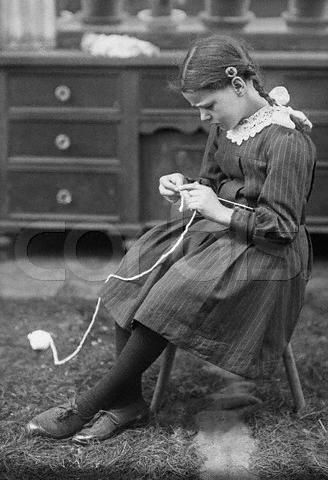 Little girl knitting.