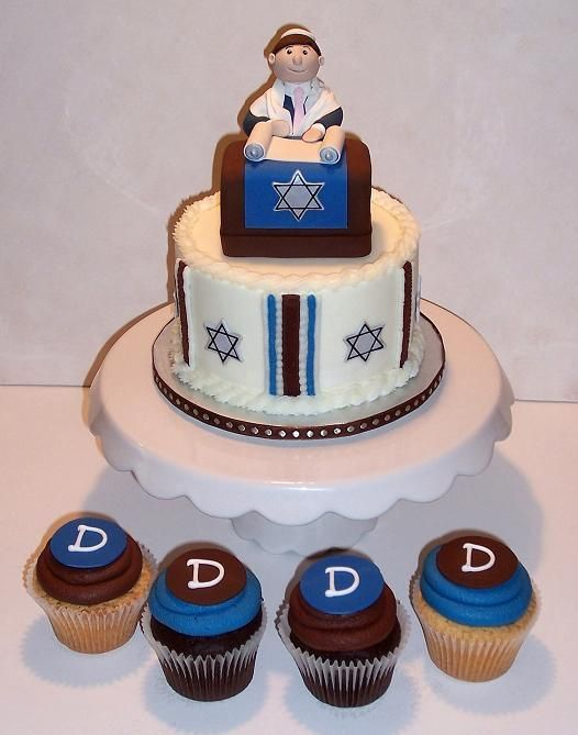 "Bar Mitzvah Cupcake Tree - Pound Cake and Devil's Food monogrammed cupcakes and 6"" topper cake for the cupcake tree in blue and brown theme.  Figure made of gumpaste, podium is RKT covered in fondant.  Cake iced in buttercream."