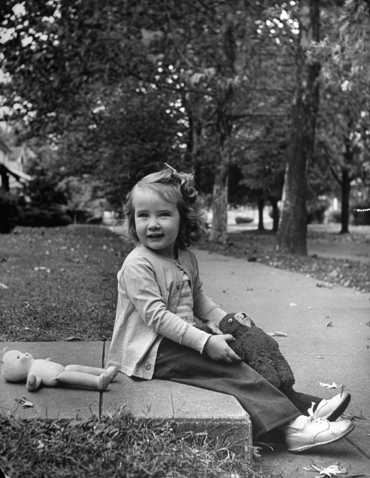 Little girl with her toys on the sidewalk, 1948